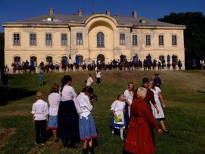 Hagyományőrző rendezvény a kastély kertjében. A háttérben a kastély hátsó fala